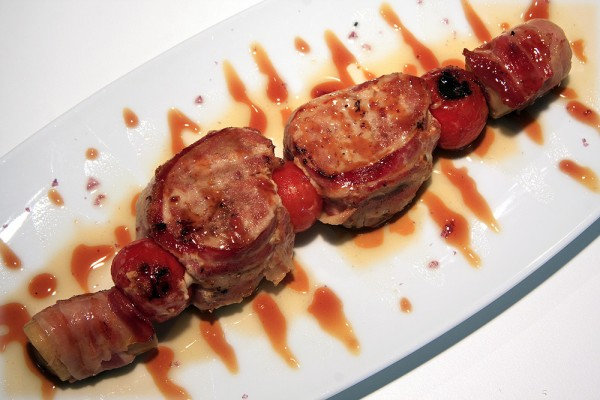 Pork sirloin brochette with banana and bacon topped with sweet and sour sauce